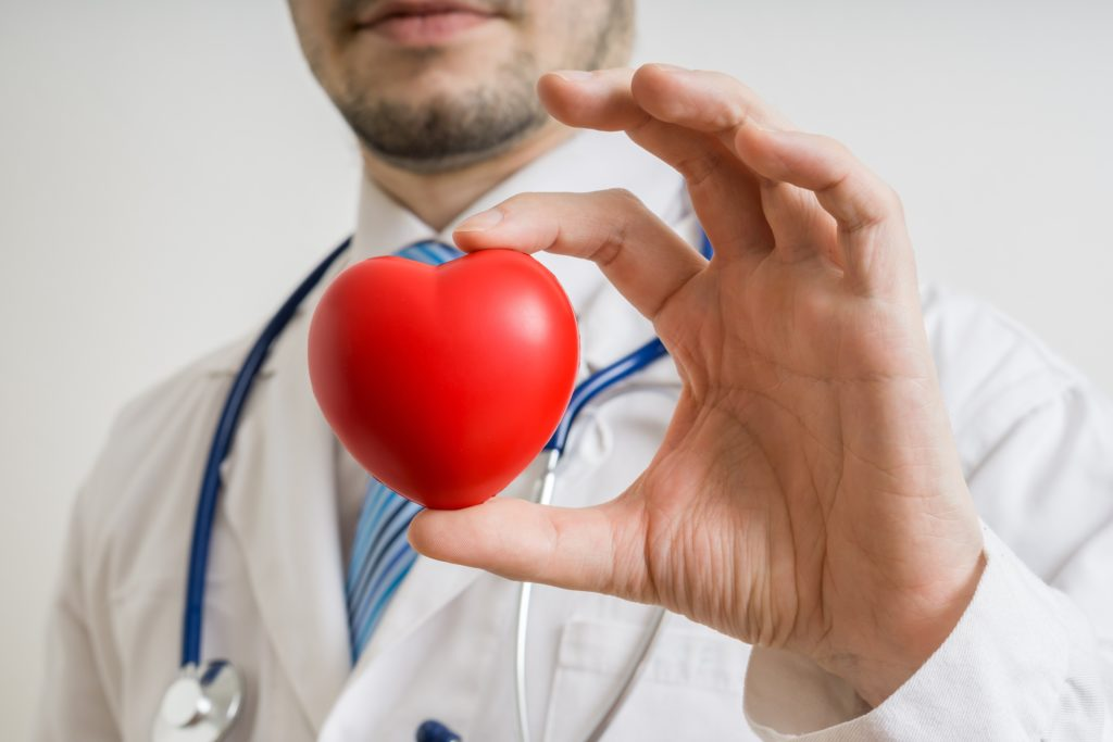 Doctor holding up a red heart